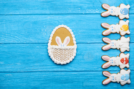 middle easter: Colorful Easter rabbit cookies background.  Rabbit cookies from the right side and big Easter egg in the middle. Top view.