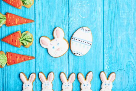 middle easter: Colorful Easter rabbit cookies background. Half of rabbits cookies at the bottom, carrot cookies on the left and a Easter Egg and bunny in the middle. Top view.