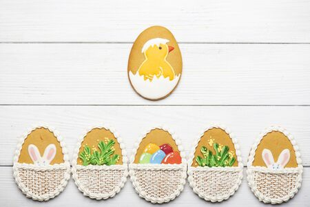 egg shape: Colorful easter cookies with different pattern in egg shape on white wooden background at the bottom. Big cookie egg with a chicken in the center. Top view Stock Photo