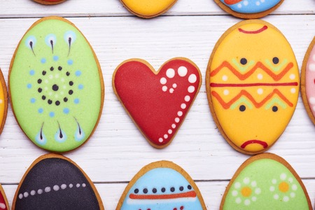 middle easter: Close view at delicious Easter cookies background. Colorful Easter cookies all over the white wooden background with heart at the middle. Eggs with different pattern icing. Top view.