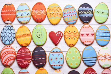 middle easter: Delicious Easter cookies background. Colorful Easter cookies all over the white wooden background with heart at the middle. Eggs with different pattern icing. Top view.