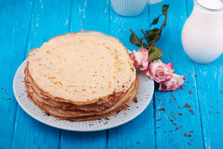 desayuno romantico: Stack of golden delicious pancakes, coffee, rose, romantic breakfast. On a blue wooden background. top view. Focus on a roses Foto de archivo