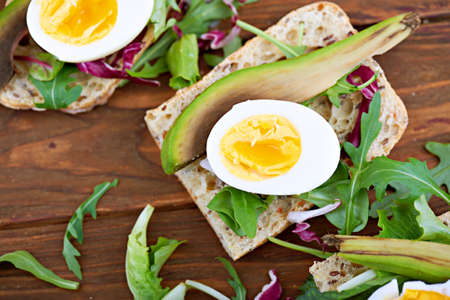sandwiche: Close view at fresh toast sandwiche with egg, avocado and salad in rustic wooden background. Shallow depth of field