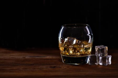 whiskey in a glass with ice in a dark wooden background.