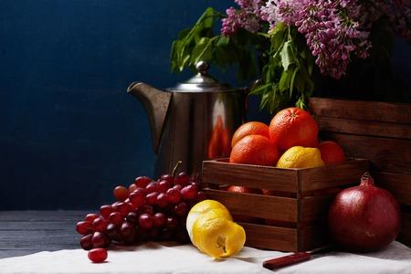 food still: Basket of grapes, oranges, lemon, pomegranate, lilac and teapot on a dark background.