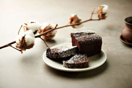 Close view at tasty chocolate cake on a white plate, with ceramic cup, cinnamon sticks and cotton flowers on a grey background
