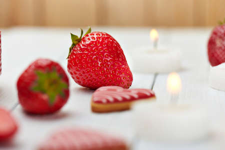 diamond candle: Juicy fresh strawberry with heart shape cookies, candles and ice on a white wooden background. Romantic set.