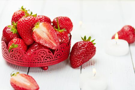diamond candle: Juicy fresh strawberry with heart shaped cookies, candle and ice on a white wooden background. Romantic set. Strawberry in a bowl. Copy space.