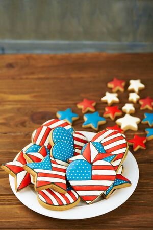 Patriotic cookies for 4th of July on a wooden background in a white plate. With scattered stars. Vertical shot Stock Photo
