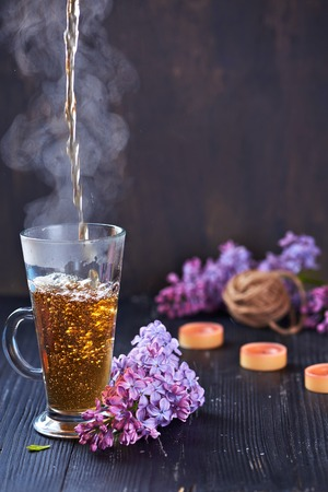 Glass of hot pouring tea on a black wooden background. With lilac and candles. Romantic atmosphere. Vertical shot.