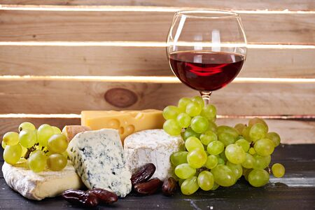 The Glass of red wine served with grapes, date fruits and the variety of cheese on a black wooden table with the wooden board on a background with a ray of light shining through it. Empty space Stock Photo