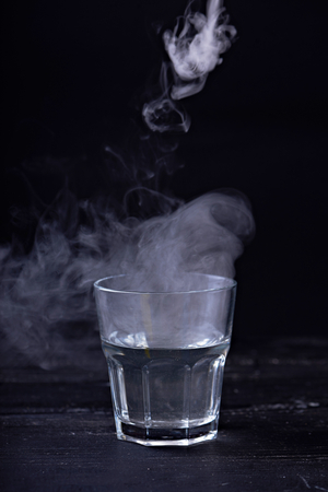Hot water with a lot of steam in a glass at a black background. Dark photo