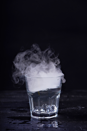 seething: Hot water with a lot of steam in a glass at a black background. Dark photo. Concept photo: three state of water - ice, water, steam. Stock Photo