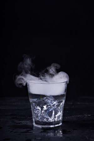 Hot water with a lot of steam in a glass at a black background. Dark photo. Concept photo: three state of water - ice, water, steam. Stock Photo