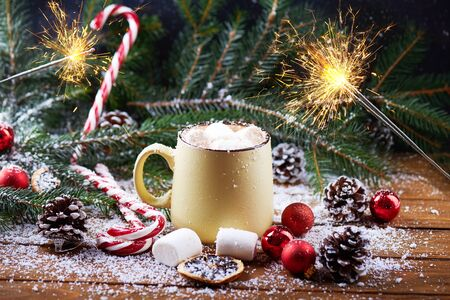mug with hot chocolate, christmas tree, tangerines, peppermint stick, sparkles and marshmallow on a snow wooden background. Dark photo. Empty space for text.