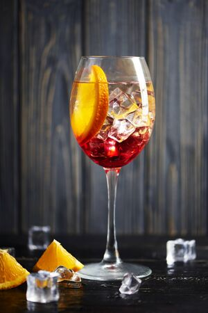 One refreshing red coctail with orange isolated on a wooden background with oranges and ice