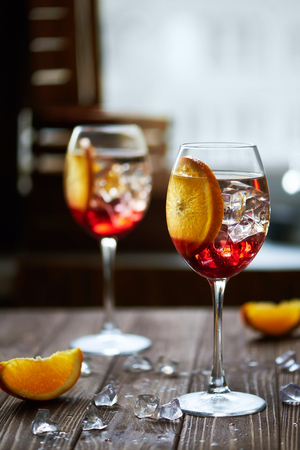 refreshing red cocktails with orange isolated on a wooden background with oranges and ice against big window