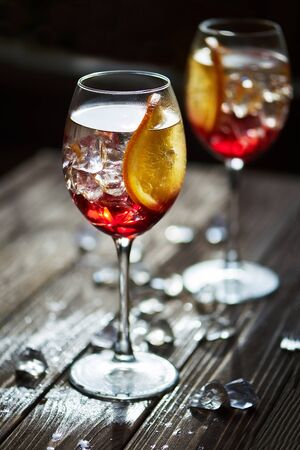 Two refreshing red cocktails with orange isolated on a wooden background with oranges and ice with backlight Stock Photo