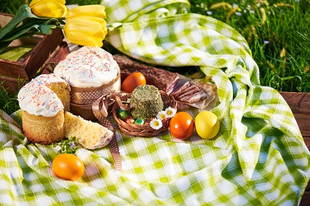 Easter cake and bright colored eggs gathered together with meat, treats and tulips on the lawn among the grass