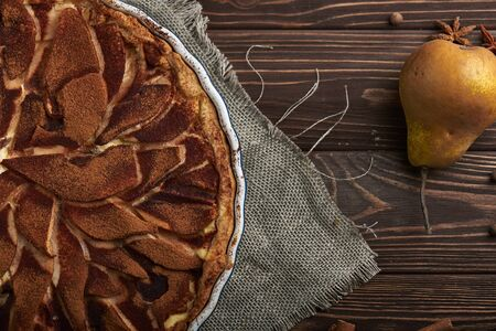 Fresh pear pie decorated with cinnamon and spices on a wooden background. Top view Stock Photo