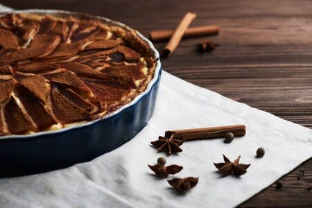 Fresh pear pie decorated with cinnamon and spices on a wooden background