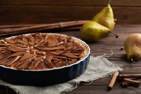 Fresh pear pie decorated with cinnamon, fresh pears and spices on a wooden background Stock Photo