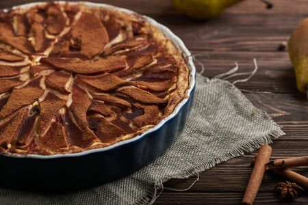 Fresh pear pie decorated with cinnamon and spices on a rustic wooden background