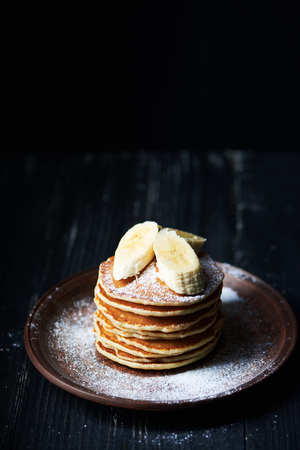 American pancakes on a plate with banana and sugar powder. Dark background. Vertical shot