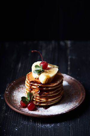 American pancakes on a plate with banana, cherry, mint caramel syrop and sugar powder. Dark background. Vertical shot Stock Photo