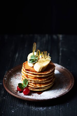 American pancakes on a plate with banana, cherry, mint, caramel syrop, love sign and sugar powder. Dark background. Vertical shot