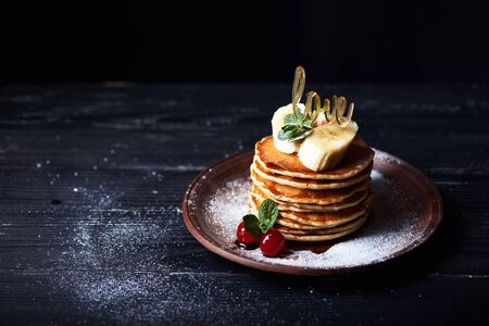 American pancakes on a plate with banana, cherry, mint, caramel syrop, love sign and sugar powder. Dark background. Stock Photo