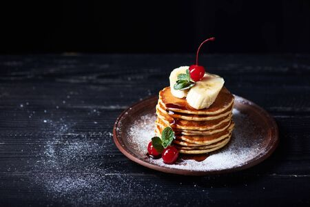 American pancakes on a plate with banana, cherry, mint caramel syrop and sugar powder. Dark background.