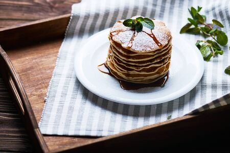 American pancakes on a plate with mint and caramel syrop. Dark background. Setted on a wooden tray