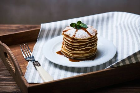 American pancakes on a plate with mint and caramel syrop. Dark background. Setted on a wooden tray with a fork Stock Photo