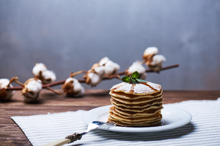 American pancakes on a plate with mint and caramel syrup. With the cotton branch on a back and a copy space. Stock Photo