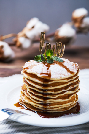 American pancakes on a plate with mint, caramel, syrup, love sign and sugar powder. With the cotton branch on a back. Vertical shot Stock Photo