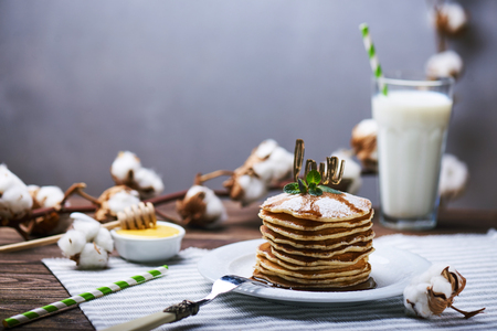 American pancakes on a plate with mint, caramel, syrup, love sign and sugar powder. With the cotton branch and a glass of milk on a back and a copy space.