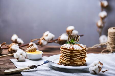 American pancakes on a plate with mint, caramel, syrup, love sign and sugar powder. With the cotton branch on a back and a copy space.