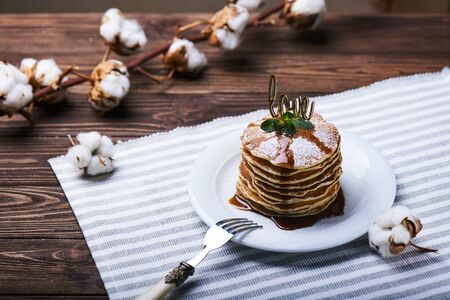 American pancakes on a plate with mint, caramel, syrup, love sign and sugar powder. With the cotton branch on a back.