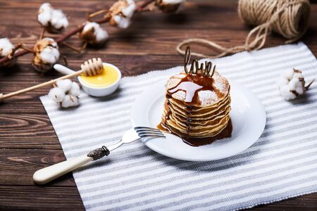 American pancakes on a plate with mint, caramel, syrup, love sign, honey and sugar powder. With the cotton branch on a back.