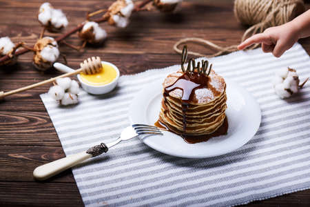 American pancakes on a plate with mint, caramel, syrup, love sign, honey and sugar powder. Also, a child hand pointing on pancakes. With the cotton branch on a back. Stock Photo
