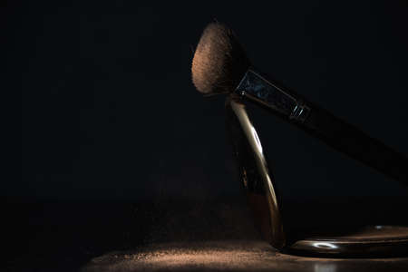 makeup brush with falling powders on black background