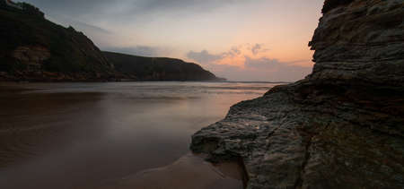 sunset on a beach with water on the shore and reflections of the sky in it