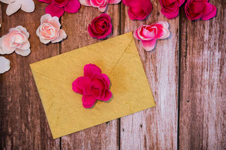 Valentine's day background with empty envelope on wooden background with roses