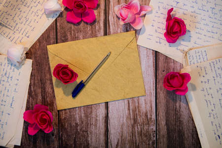 Valentine's day background with romantic letters, pen and roses on wood