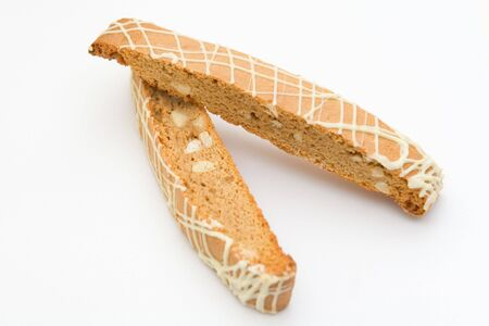 two frosted and nutty biscotti on a white background.  Stock Photo