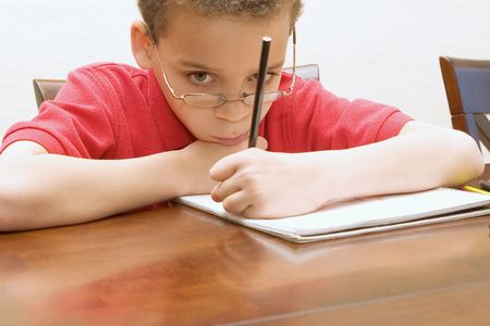 reluctant: Left handed young boy wearing glasses reluctant to do homework not paying attention, staring into space.