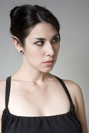Young hispanic woman looking away from the camera, looking annoyed photo