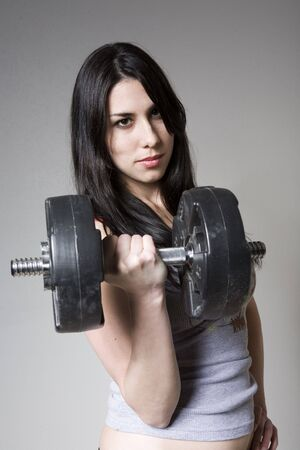 young woman getting in shape with dumbbell photo