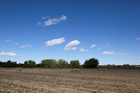 Wide angle view of baled hay field against dramatic blue sky photo